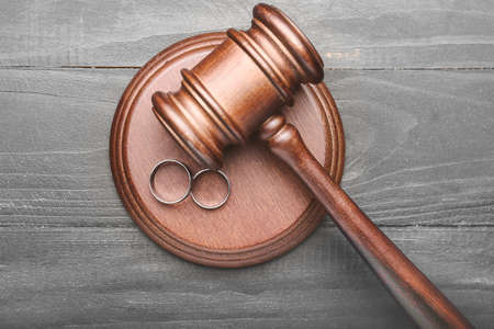 Judge's gavel and rings on wooden background. Concept of divorce