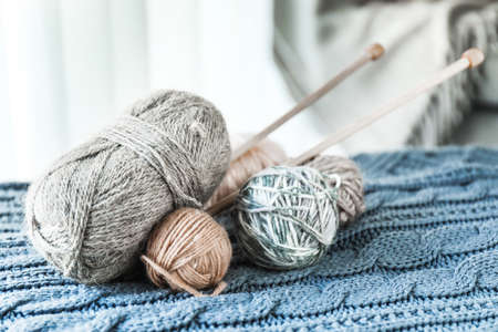 Knitting yarn and needles on plaid at home Foto de archivo