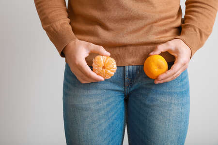 Young man with tangerines on gray background. Urology concept