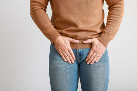 Young man with urologic disease on light background