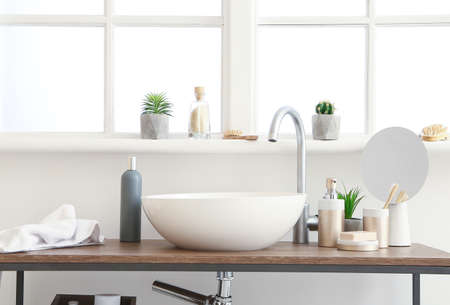 Body care cosmetics with accessories on stand with sink in bathroom