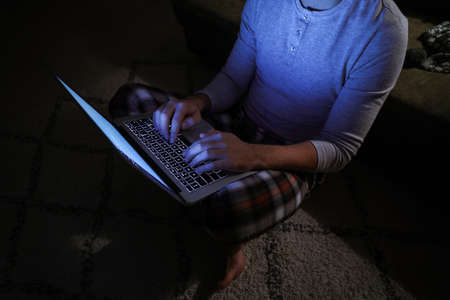 Man with laptop late in evening at home