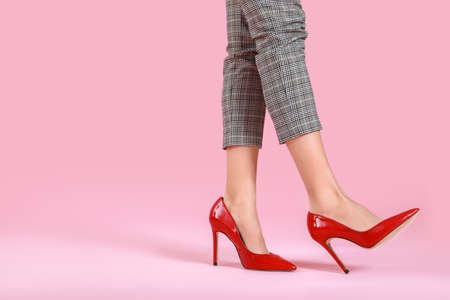 Legs of young woman in high-heeled shoes on color background