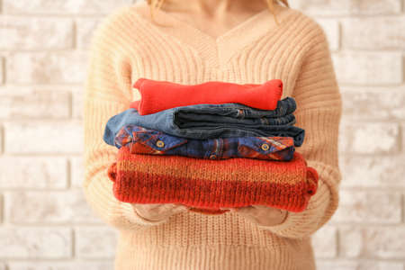 Woman with stack of warm clothes on brick background