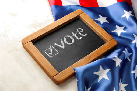 Chalkboard with text VOTE and USA flag on light background