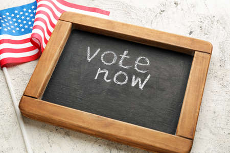 Chalkboard with text VOTE NOW and USA flag on light background