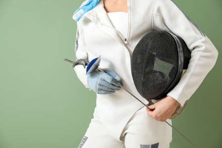Young female fencer on color background