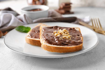 Plate with fresh bread and chocolate paste on table