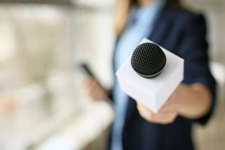 Female journalist with microphone in office, closeup