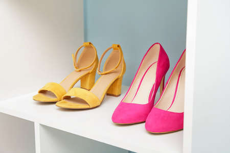 Shelf unit with stylish shoes near color wall