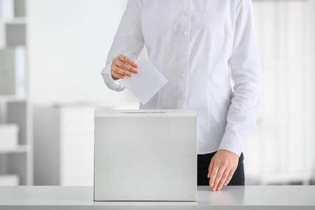 Voting woman near ballot box indoors Stock Photo