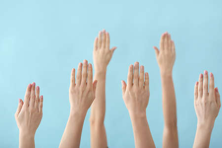 Hands of voting people on color background