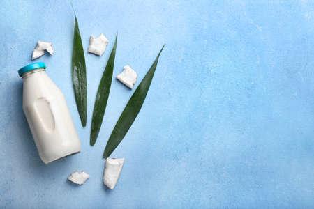 Bottle of coconut milk on color background