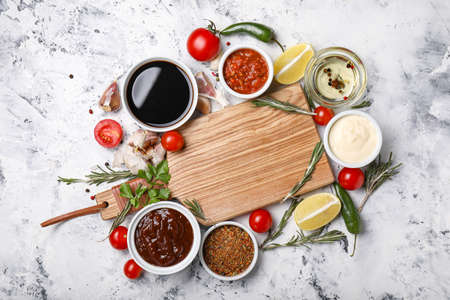Bowls with tasty sauces, ingredients and wooden board on white background Imagens