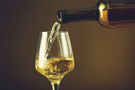Pouring of wine into glass on color background