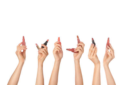 Female hands with lipsticks on white background