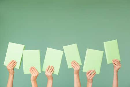 Female hands with books on color background Reklamní fotografie