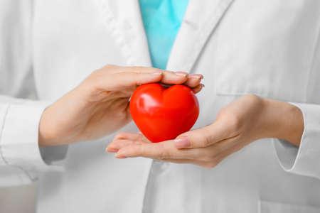 Female cardiologist with red heart closeup Foto de archivo