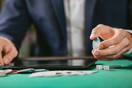 Man with tablet computer playing poker online, closeup