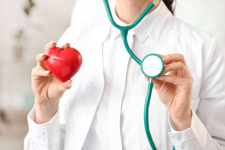 Female cardiologist with red heart in modern clinic Stock Photo