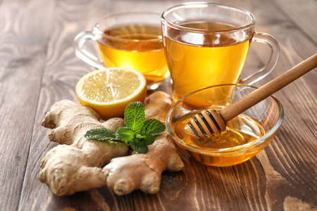 Cups of healthy drink with lemon, ginger and honey on wooden table