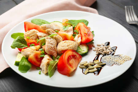 Plate with tasty chicken salad on table Stockfoto