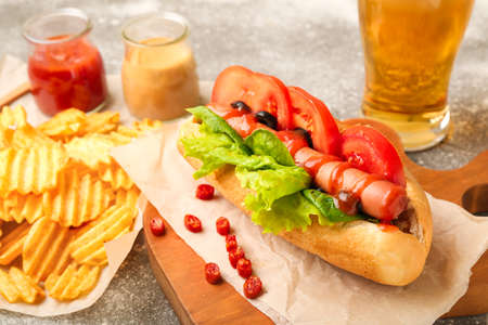 Tasty hot dog, chips and beer on table Banque d'images