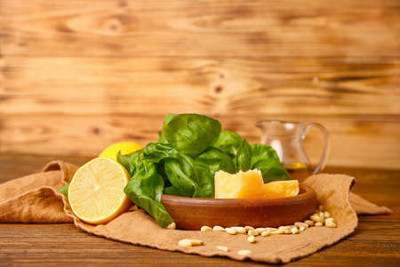 Ingredients for pesto sauce on wooden background