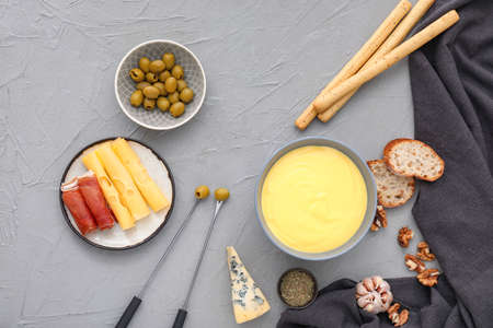 Cheese fondue with snacks on gray background