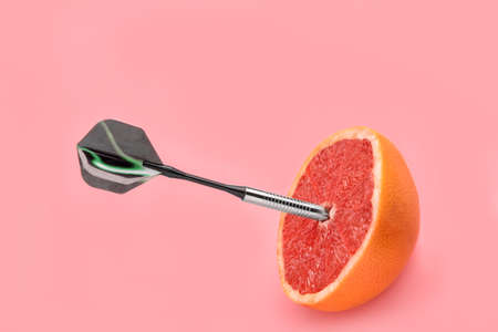 Dart with half of grapefruit on color background Stock Photo