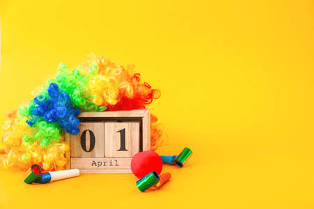Calendar with date of April Fool's Day and party decor on color background