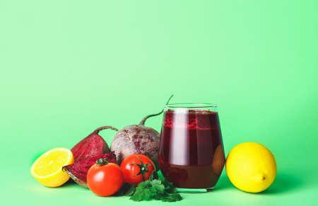 色の背景に新鮮な野菜ジュースのグラス