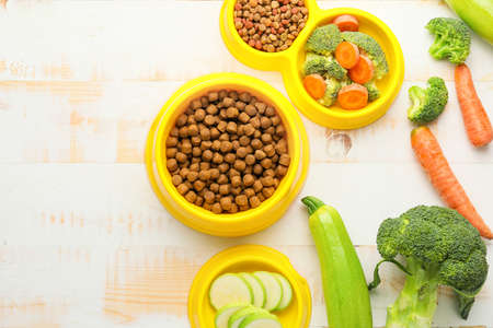 Composition with dry pet food and natural products on wooden background
