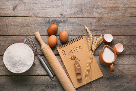 Ingredients for preparing bakery, notebook and utensils on wooden background