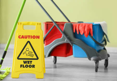 Caution sign with janitor's trolley indoors