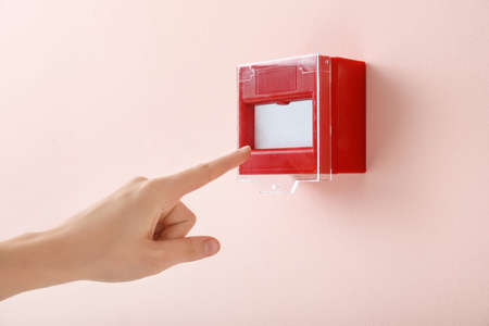 Hand of person near manual call point mounted on wall