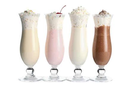 Glasses of tasty milkshakes on white background