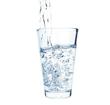 Pouring of fresh water in glass on white background