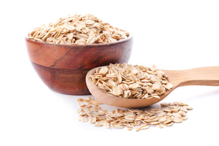 Bowl and spoon with raw oatmeal on white background
