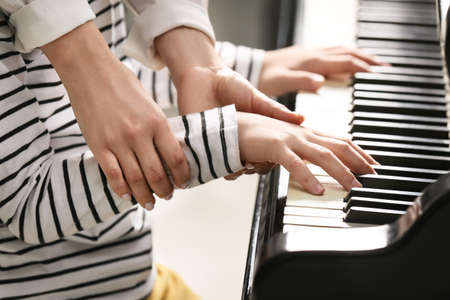 Private music teacher giving piano lessons to little boy, closeup