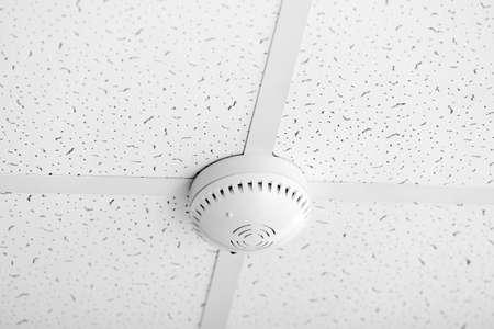 Modern smoke detector on ceiling