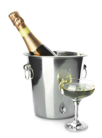Bucket with bottle and glass of champagne on white background