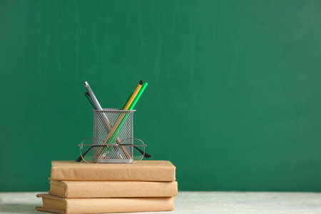Books and stationery on table in classroom Stock Photo