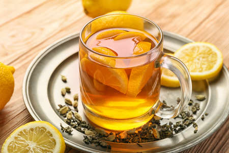 Cup of hot tea with lemon and cardamom on table Stockfoto