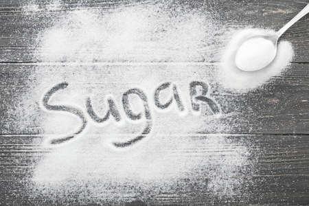 White sugar on wooden background