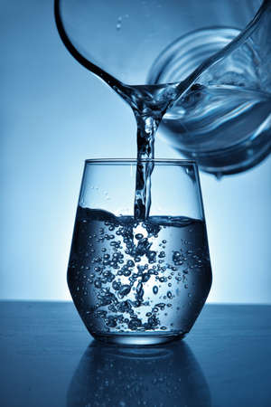 Pouring of fresh water in glass on color background