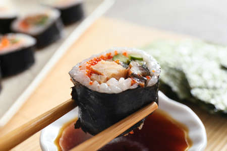 Dipping of tasty sushi roll into soy sauce, closeup