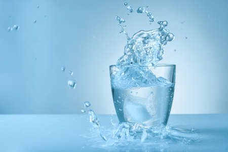 Glass of fresh water with splash on color background