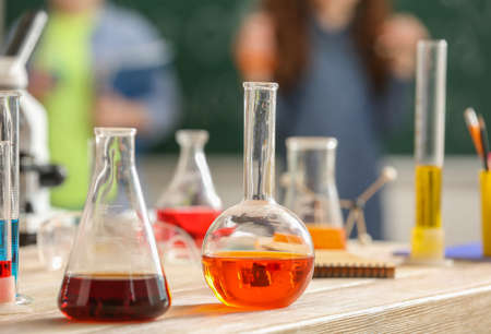 Laboratory glassware with liquids on table in classroom Stock Photo