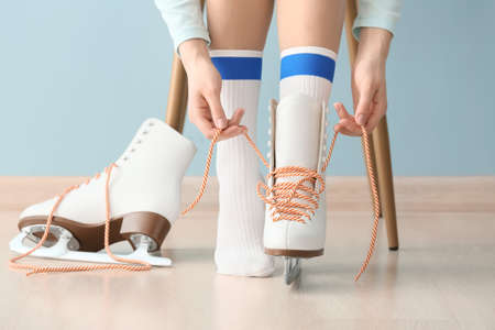 Young woman tying laces on ice skate shoes indoors